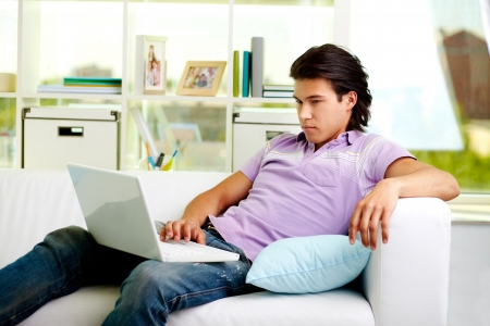 Portrait of attractive guy sitting with laptop at home photo