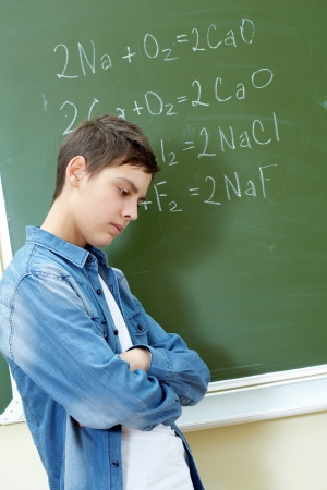 formulae: Sad guy standing by the blackboard with chemical formulae on it
