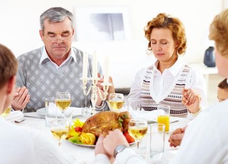 familia orando: Retrato de la familia grande que se sienta en la mesa de fiesta y oraci�n antes de la cena