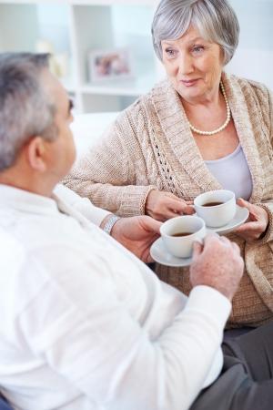 mujer tomando cafe: Retrato de hombre maduro y su esposa beber t� e interactuantes