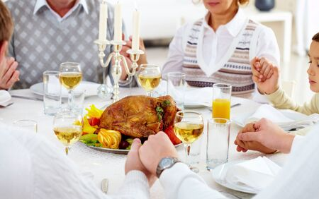 Family members giving thanks to God at festive table with roasted turkey on it Stock Photo - 15609330