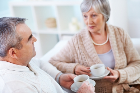 Portrait of mature man and his wife drinking tea and interacting photo