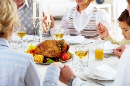 thanksgiving dinner: Family members giving thanks to God at festive table with roasted turkey on it