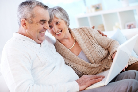 Portrait of mature man and his wife working with laptop at home Stock Photo - 15609743