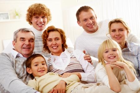 padres e hijos felices: Retrato de matrimonios mayores y jóvenes con sus hijos descansando en su casa