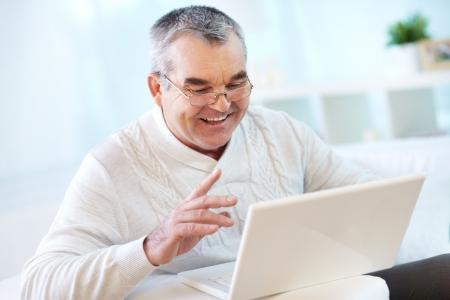 personas comunicandose: Retrato de hombre maduro de trabajo con el ordenador port�til en casa