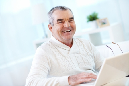 older men: Portrait of mature man working with laptop and looking at camera