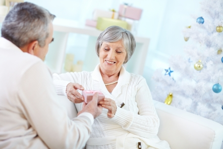 Portrait of mature woman talking small giftbox from her husband Stock Photo - 15609815
