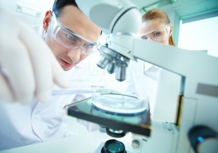 laboratories: Serious clinician studying chemical element in laboratory with his assistant near by