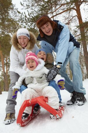 Happy kids and their parents riding on sledge in park Stock Photo - 15610836