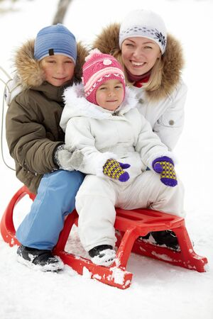 Happy kids sitting on sledge in park with their mother near by Stock Photo - 15638038