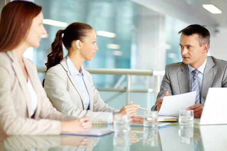 Serious boss looking at his employees while commenting a document at meeting photo