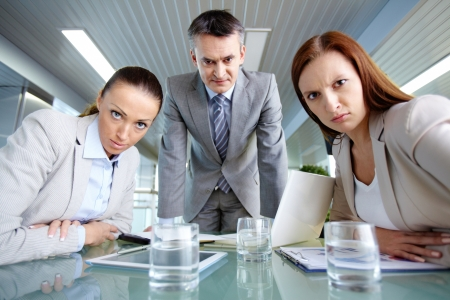 serious meeting: Serious boss his two employees looking at camera with displeasure Stock Photo