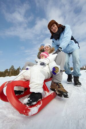 Happy kids and their parents riding on sledge in park Stock Photo - 15609717