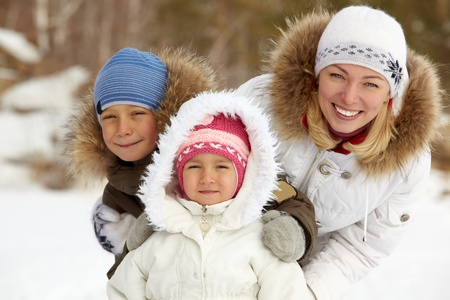 Happy kids and their mother in winterwear looking at camera photo
