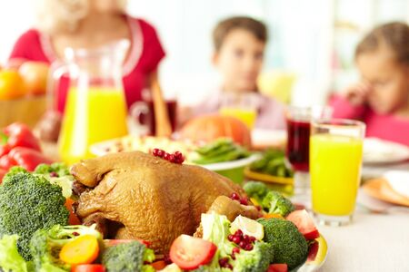 christmas turkey: Close-up of roasted turley served with broccoli on background of siblings and woman Stock Photo