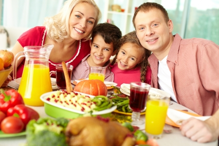 thanksgiving adult: Portrait of happy family sitting at festive table and looking at camera Stock Photo
