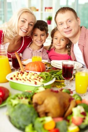 högtider: Porträtt av lyckliga familjen sitter vid festliga bord och tittar på kameran