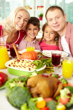 Christmas feast: Portrait of happy family sitting at festive table and looking at camera Stock Photo