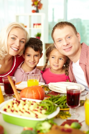 Portrait of happy family sitting at festive table and looking at camera Stock Photo - 15609901