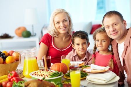 familia cristiana: Retrato de familia feliz sentado en la mesa festiva y mirando a la cámara