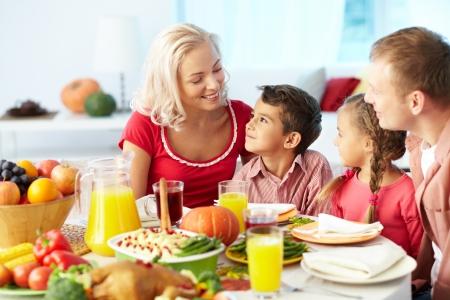 familia cristiana: Retrato de familia feliz sentado en la mesa festiva y chat Foto de archivo