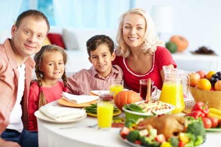 Portrait of happy family gathered at festive table on Thanksgiving Day photo