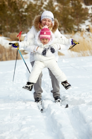 winter sports: Little girl and her mother skiing in park