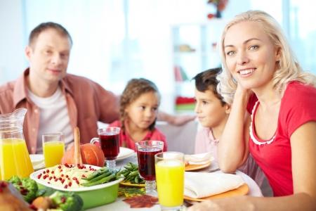 familia cristiana: Retrato de la mujer feliz que se sienta en la mesa festiva y mirando a la cámara con su familia en el fondo Foto de archivo