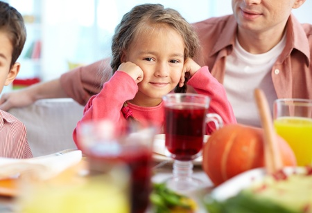 a little dinner: Portrait of happy girl sitting at festive table and looking at camera with her father and brother near by