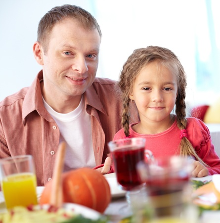 Portrait of happy girl and her father sitting at festive table and looking at camera Stock Photo - 15610886