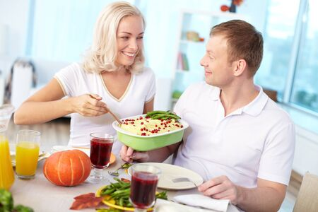 Portrait of happy couple sitting at festive table and going to eat mashed potatoes Stock Photo - 15609524