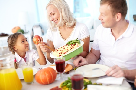 Portrait of happy couple and their daughter sitting at festive table and going to eat mashed potatoes Stock Photo - 15611041
