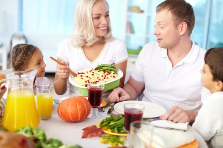Portrait of happy couple and their kids sitting at festive table and going to eat mashed potatoes Stock Photo - 15609738