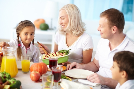 Portrait of happy parents and two children sitting at festive table and going to eat mashed potatoes Stock Photo - 15609699