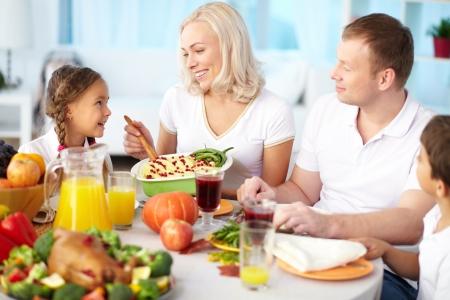 PURE: Retrato de pareja feliz y sus niños que se sientan en la mesa festiva y va a comer puré de patatas Foto de archivo