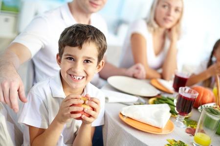 familia cristiana: Retrato de ni�o feliz con manzana sentado en la mesa festiva y mirando a la c�mara con su familia en el fondo
