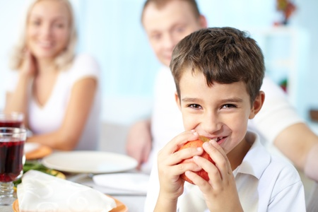 Portrait of happy boy with apple sitting at festive table and looking at camera with his parents on background Stock Photo - 15609446