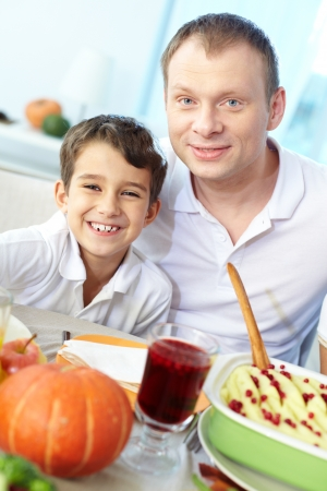 Portrait of happy boy and his father sitting at festive table and looking at camera Stock Photo - 15611017