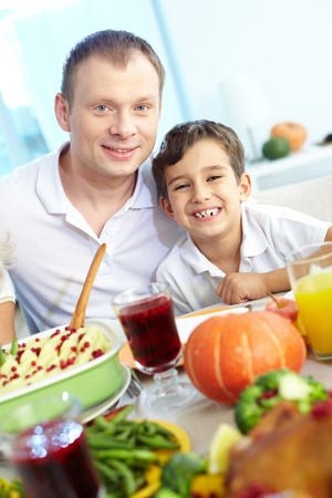 Portrait of happy boy and his father sitting at festive table and looking at camera Stock Photo - 15610078