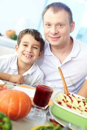 Portrait of happy boy and his father sitting at festive table and looking at camera Stock Photo - 15609865