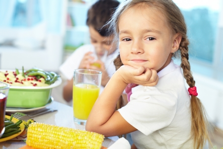 Portrait of happy girl sitting at festive table and looking at camera Stock Photo - 15610953