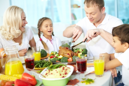 Portrait of happy couple and their children sitting at festive table and going to eat roasted turkey Stock Photo - 15609808