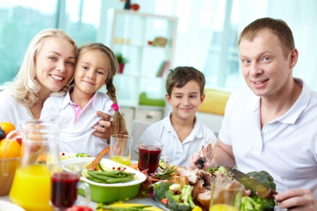 beautiful thanksgiving: Portrait of happy family sitting at festive table and looking at camera Stock Photo