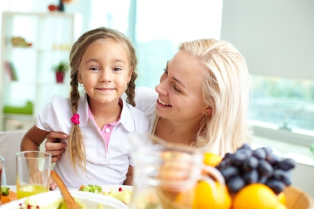 Portrait of happy woman and her daughter sitting at festive table Stock Photo - 15606892