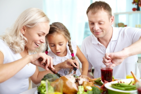 thanksgiving adult: Portrait of happy woman cutting turkey at festive table with her husband and daughter near by Stock Photo