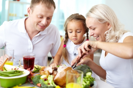 family celebration: Portrait of happy couple and their daughter sitting at festive table and going to eat roasted turkey