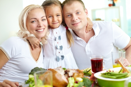Portrait of happy couple and their daughter sitting at festive table and looking at camera Stock Photo - 15609701