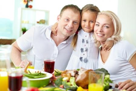 familia cristiana: Retrato de la feliz pareja y su hija que se sientan en la mesa festiva y mirando a la c�mara