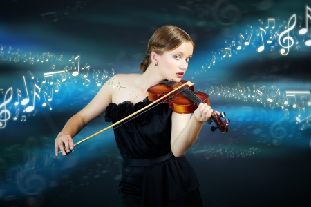Portrait of a young female playing the violin and looking at camera over creative background photo